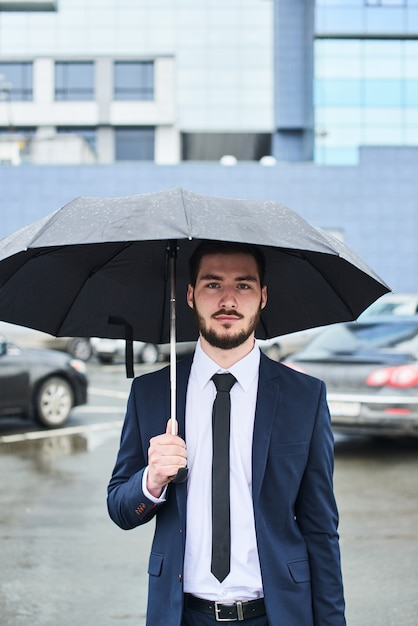 Le Gars En Costume Sur Le Parking Avec Un Parapluie à La Main Photo Premium