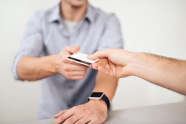 Le gars donne la carte de crédit au vendeur. Photo Premium