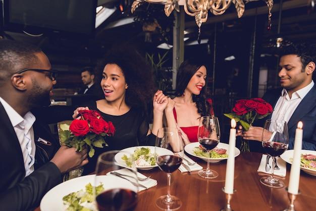 Les gars donnent des roses à leurs filles dans un restaurant. Photo Premium