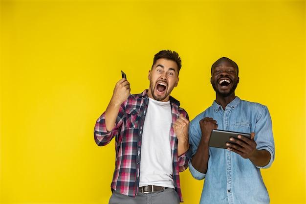 Un Gars Européen Et Afro-américain Est Sincèrement Excité Avec La Tablette Et La Carte De Crédit En Mains Photo gratuit