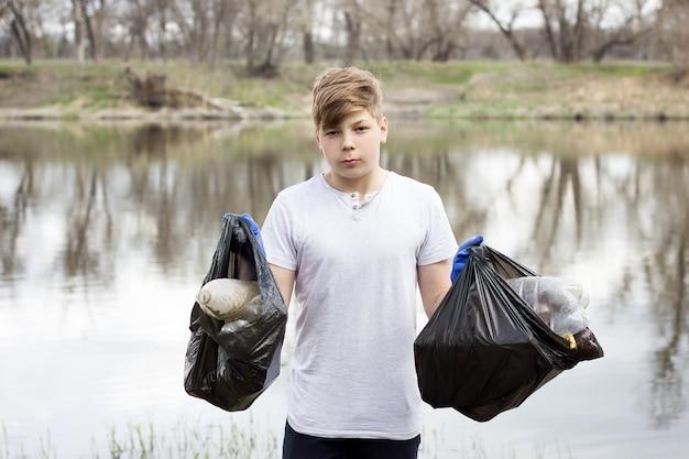 Gars jeune volontaire ramasse les ordures sur les rives de la rivière au printemps. Photo Premium