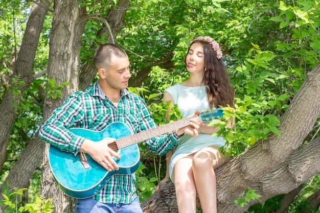 Le Gars Joue De Sa Guitare Bien-aimée. Fille Avec Plaisir Avec Les Yeux Fermés écoute Assis Sur Un Arbre Photo Premium
