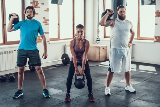 Les gars mettent des poids sur leurs épaules et une fille fait un squat. Photo Premium