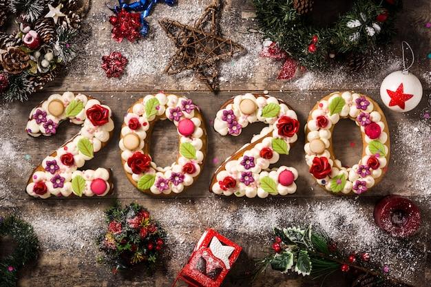 Gâteau 2020 et ornements de noël sur une table en bois. concept de nouvel an. Photo Premium