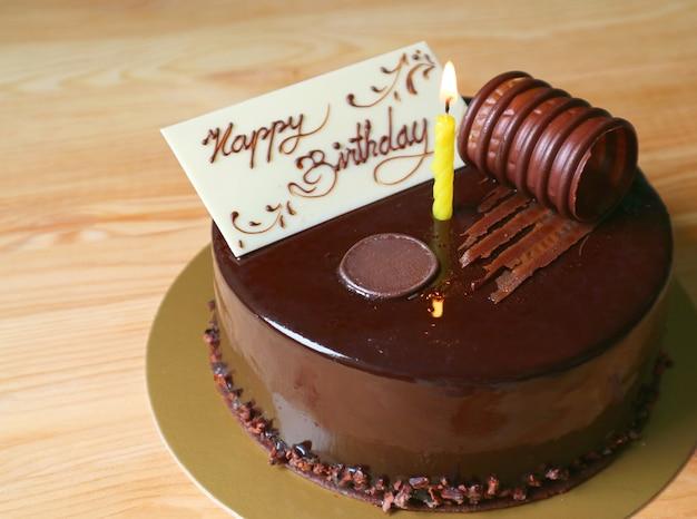 Gâteau d'anniversaire au chocolat moelleux garni d'une carte de voeux au chocolat blanc comestible et d'une bougie d'éclairage Photo Premium