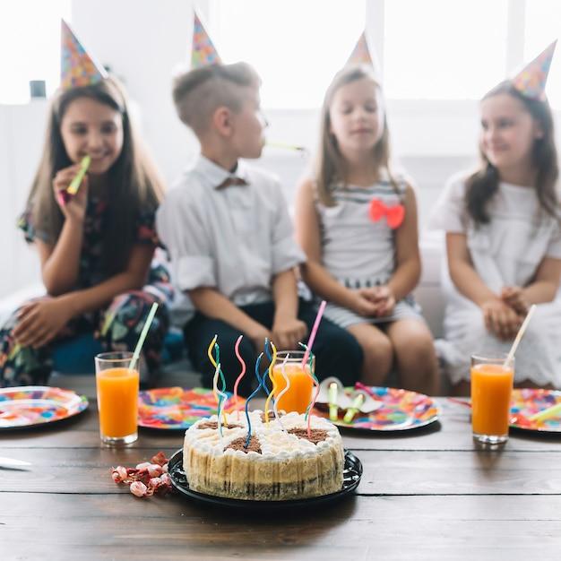 Gâteau d'anniversaire et boissons près des enfants Photo gratuit