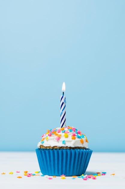 Gâteau d'anniversaire avec une bougie sur fond bleu Photo gratuit