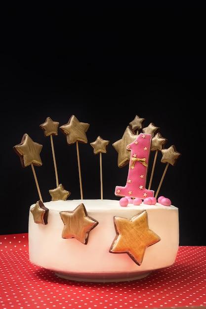 Gâteau D'anniversaire Décoré De Rose Numéro 1 Et D'étoiles Dorées De Pain D'épice Sur Un Mur Sombre. Photo Premium