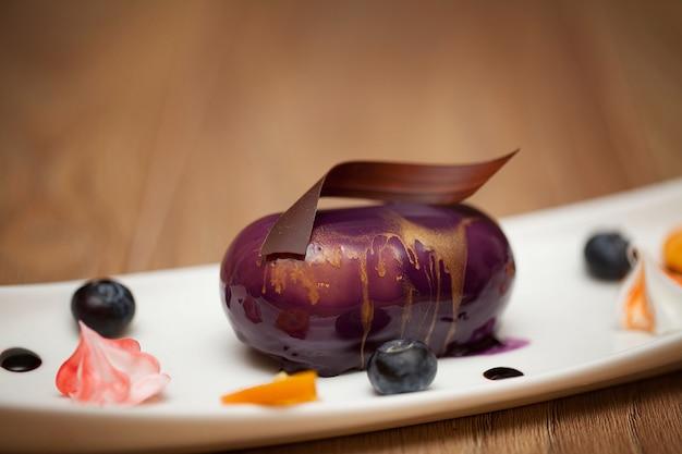 Gâteau au chocolat arrosé de glaçage or violet sur un fond en bois Photo Premium