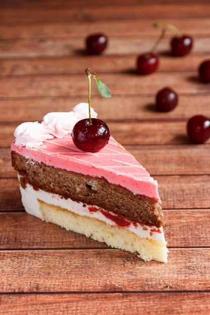 Gâteau au chocolat aux cerises sur fond en bois. Photo Premium