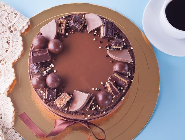 Gâteau au chocolat avec des bonbons et ruban sur une table bleue Photo Premium