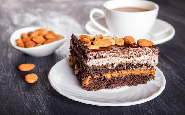 Gâteau au chocolat avec caramel, cacahuètes et amandes sur une surface en bois noire. Photo Premium