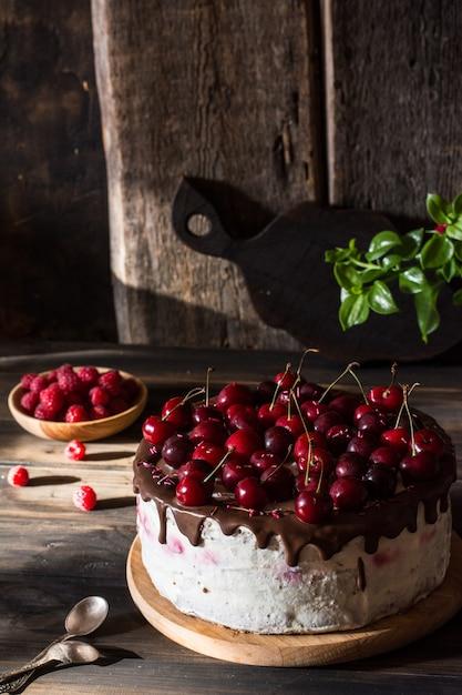 Gâteau au chocolat avec crème fouettée. cerise au chocolat. framboise. Photo Premium