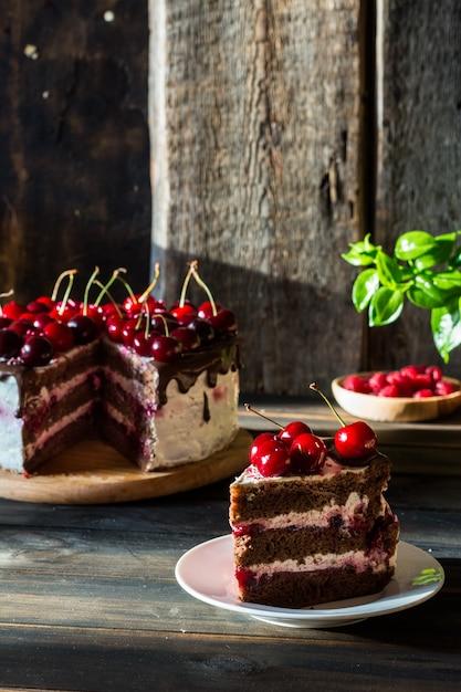 Gâteau au chocolat avec crème fouettée. gâteau aux cerises au chocolat. framboise dans une assiette en bois. Photo Premium