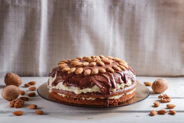 Gâteau au chocolat fait maison avec de la crème de lait et des amandes sur une table en bois blanche. Photo Premium