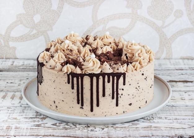 Gâteau au chocolat avec glaçage crème sur fond en bois blanc grunge Photo Premium