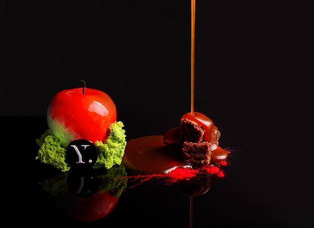Gâteau au chocolat avec mousse au caramel dans le glaçage miroir. avec des noix. sur le fond noir réflexion. Photo Premium