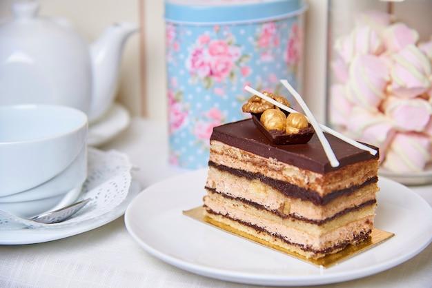 Gâteau au chocolat avec des noix sur une assiette près d'une tasse, théière et pot de guimauves. Photo Premium