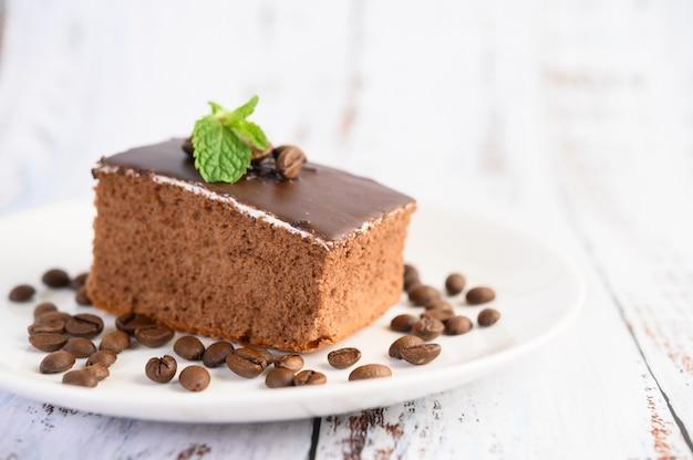 Gâteau Au Chocolat Sur Une Plaque Blanche Avec Des Grains De Café Sur Une Table En Bois Photo gratuit