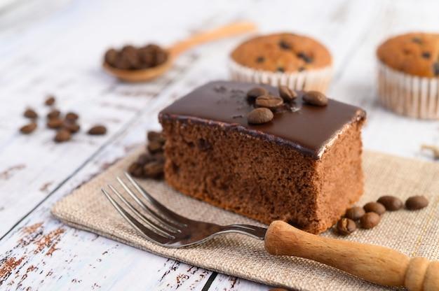 Gâteau Au Chocolat Sur Le Sac Et Les Grains De Café Avec Une Fourchette Sur Une Table En Bois. Photo gratuit