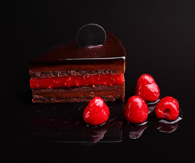 Gâteau au chocolat zacher à la framboise, mousse dans le reflet du miroir, section. sur le fond noir Photo Premium