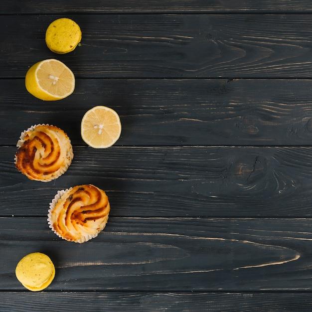 Gâteau au citron meringuée et macarons au citron coupé en deux sur un fond texturé en bois noir Photo gratuit
