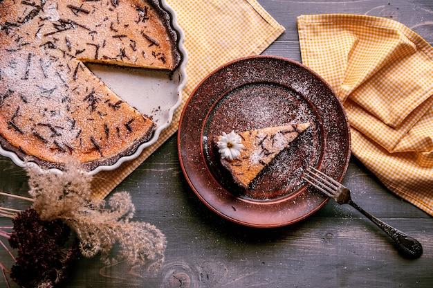 Gâteau Au Four Sous Forme De Céramique Saupoudré De Tranches De Chocolat Sur Une Table En Bois. Tranche De Gâteau Posée Sur Une Assiette En Argile Et Décorée De Fleurs Photo Premium