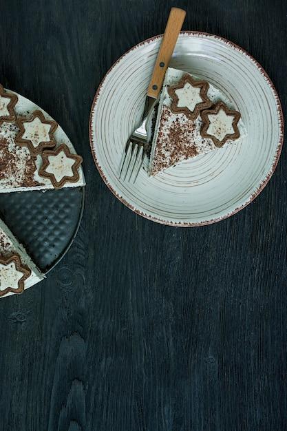 Le gâteau au fromage cottage est décoré de biscuits et de chocolat noir râpé sur du bois foncé Photo Premium