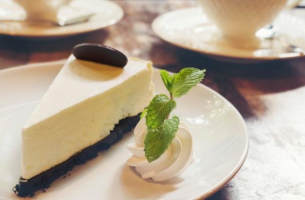 Gâteau au fromage avec une tasse de café chaud dans un café Photo gratuit
