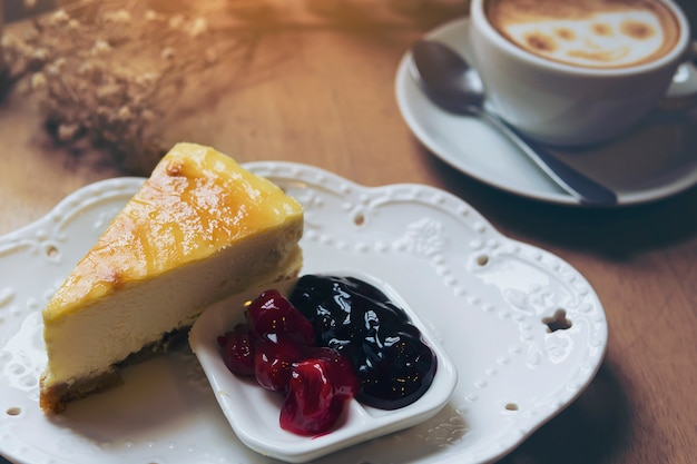 Gâteau au fromage avec une tasse de café chaud sur une table en bois Photo gratuit