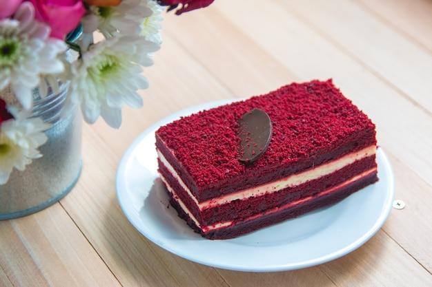 Gâteau au fromage de velours rouge sur assiette et bouquet de roses Photo Premium