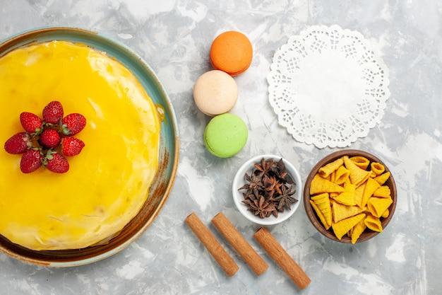 Gâteau Au Sirop Jaune Vue De Dessus Avec Des Macarons Français Sur Fond Blanc Photo gratuit