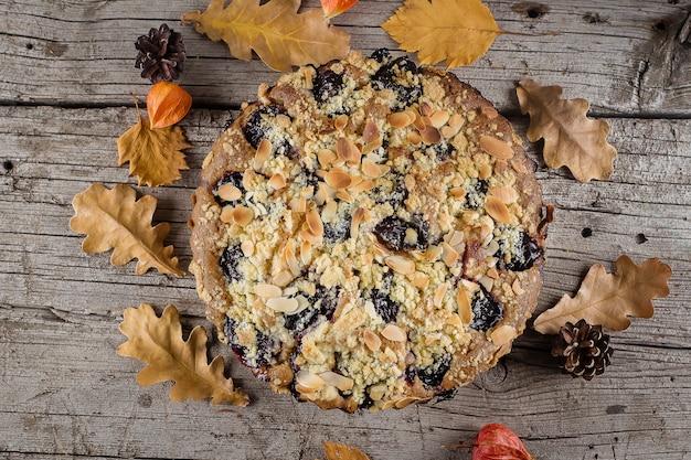 Gâteau automne maison aux noix et prunes sur fond en bois, vue de dessus, espace copie Photo Premium