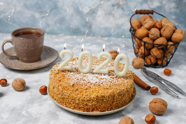 Gâteau aux carottes avec des bougies 2020 et une tasse de thé sur du béton gris Photo gratuit