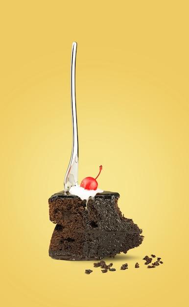 Gâteau aux cerises au chocolat isolé avec une fourchette de dos sur fond jaune. Photo Premium