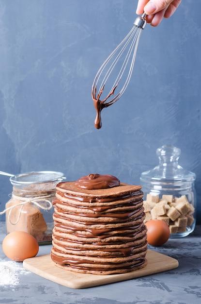 Gâteau aux crêpes. une pile de crêpes au chocolat avec crème au chocolat et amandes. Photo Premium
