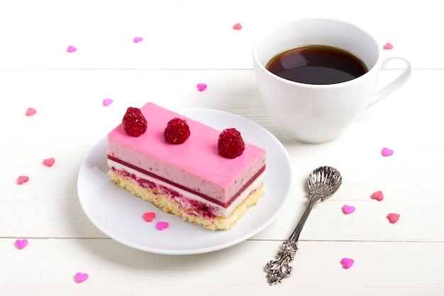 Gâteau aux fraises, café americano, bonbons coeurs sur un fond en bois blanc Photo Premium