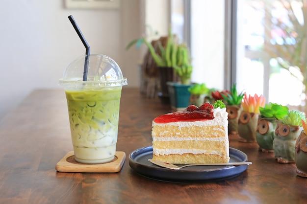 Gâteau Aux Fraises Dans Un Plateau En Métal Et Latte Au Thé Vert Matcha Glacé Dans Une Tasse à Emporter Sur Une Table En Bois Au Café. Photo Premium