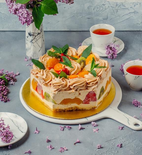 Gâteau aux fruits avec du thé noir sur la table Photo gratuit