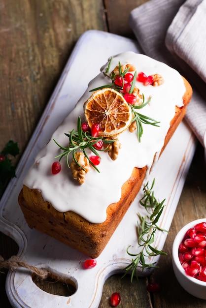Gâteau aux fruits saupoudré de glaçage, de noix, de noyaux de grenade et de gros plan orange sec. gateau maison vacances noel et hiver Photo Premium