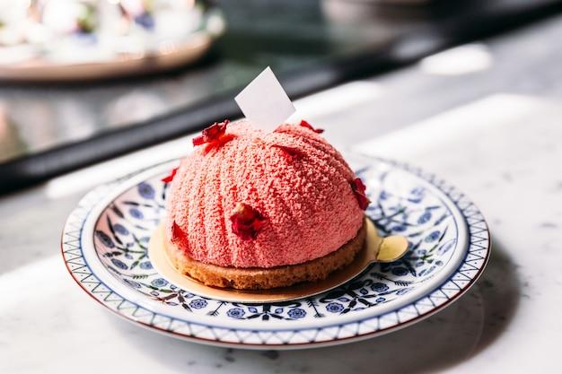 Gâteau aux mousses à la rose et au litchi, décoré de pétales de rose et d'une assiette en chocolat blanc. Photo Premium