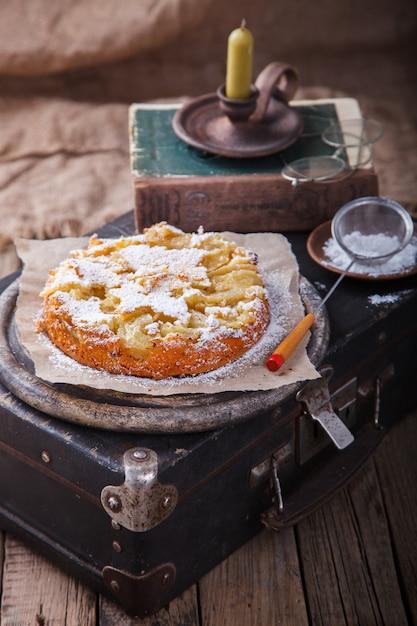 Gâteau Aux Pommes Sur Une Valise Vintage Au Sucre En Poudre. Photo Premium