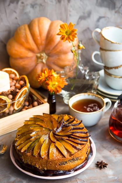 Gâteau aux prunes décoré avec des prunes tranchées parmi le décor d'automne Photo Premium