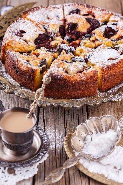 Gâteau aux prunes avec du sucre en poudre et une tasse de café Photo Premium
