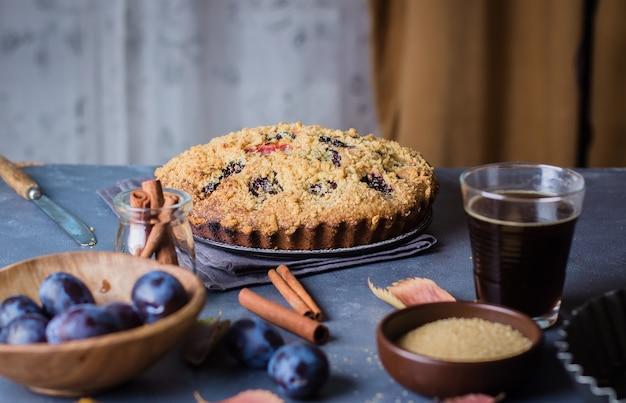 Gâteau aux prunes rustique fait maison sur fond de béton foncé. tarte aux fruits sucrés. Photo Premium