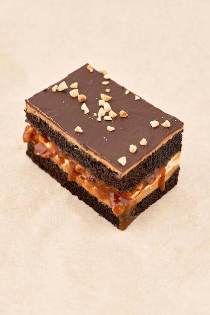 Gâteau Biscuit Noir Avec Une Couche De Crème Et Fondant Au Chocolat, Saupoudré De Noix Râpées, Cadre Vertical Photo Premium