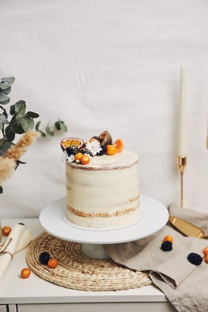 Gâteau Blanc Aux Baies Et Fruits De La Passion à Côté D'une Plante Photo gratuit
