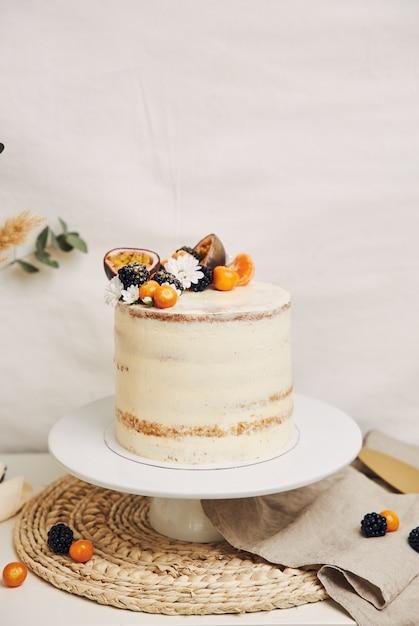 Gâteau Blanc Aux Baies Et Fruits De La Passion Avec Des Plantes Derrière Photo gratuit