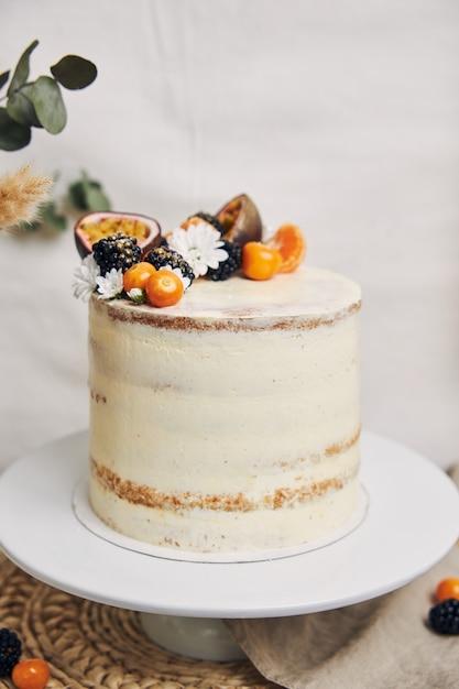 Gâteau Blanc Aux Fruits Rouges Et Fruits De La Passion à Côté D'une Plante Derrière Un Fond Blanc Photo gratuit