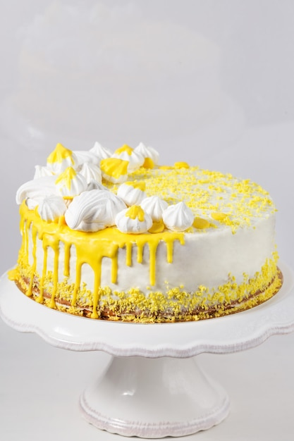 Gâteau blanc tendance avec ganache au chocolat jaune, guimauve et meringues sur un présentoir à gâteaux Photo Premium